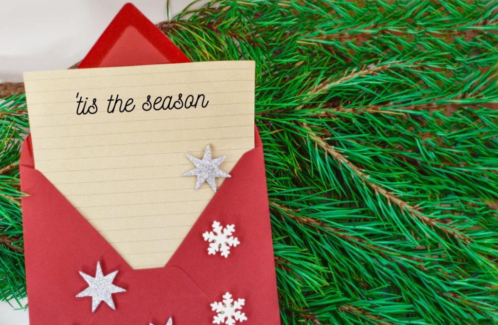 "A letter in a red envelope saying ""'Tis the season"""