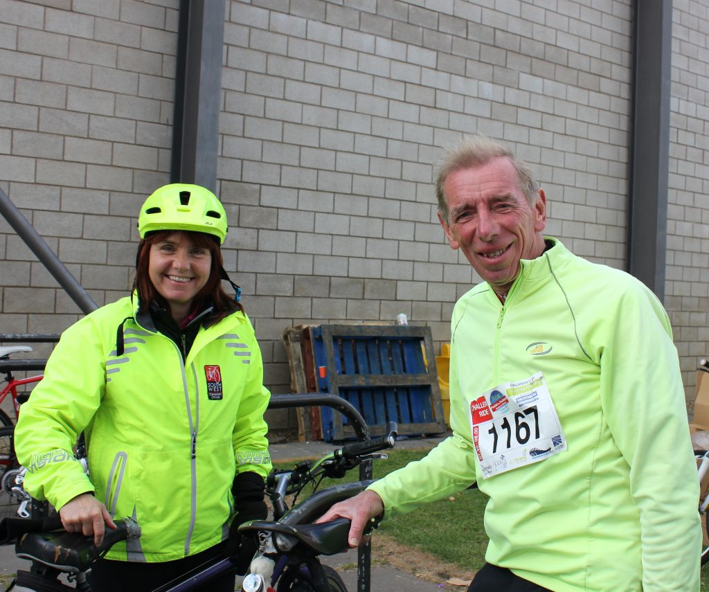 Two people in high vis clothing standing next to their bicycles.